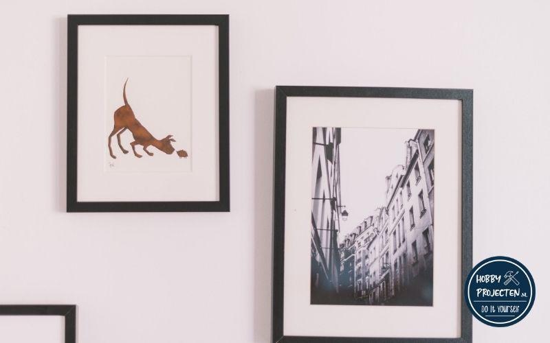 twee fotolijsten aan een muur