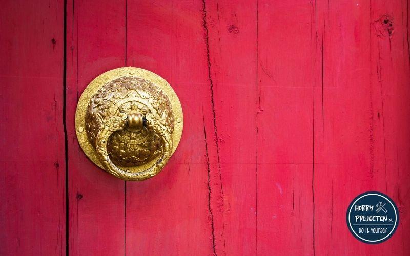 Gouden deurknop op een rode deur